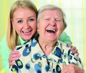 Senior woman with her caregiver. Happy and smiling.