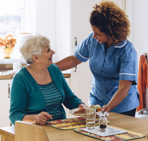 Caregiver and resident smiling together over a meal