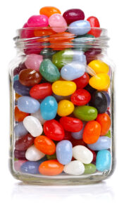 A clear jar with many brightly colored jelly bean candies
