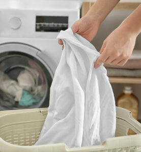 Hands pulling laundry out of a basket