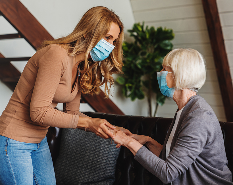Caregiver in a medical mask with a senior woman